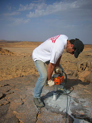 Geologist Seb Luning drilling into Palaeozoic sandstones, southern Libya.